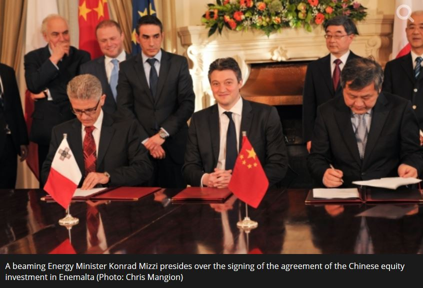 Konrad Mizzi - with a very telling facial expression - signs the Malta government deal with the Chinese government's power company in March 2014. This photograph is from Malta Today.